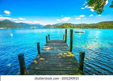 Orta Lake landscape. Wooden pier or jetty and Orta San Giulio village and island, Piedmont, Italy, Europe.