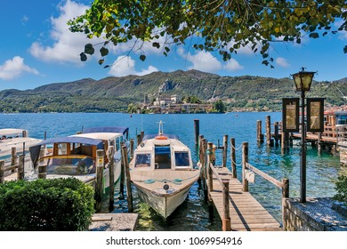 ORTA SAN GIULIO, ITALY - AUGUST 12, 2017: Boats anchored along small wooden pier on Lake Orta - famous and very popular tourist resort and travel destination located in Piedmont, Northern, Italy.