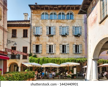 Orta San Giulio, Lake Orta, Italy - June 29, 2019  Restaurants at Piazza Motta in Orta San Giulio at Orta Lake in Italy being visited by tourists during a summer afternoon