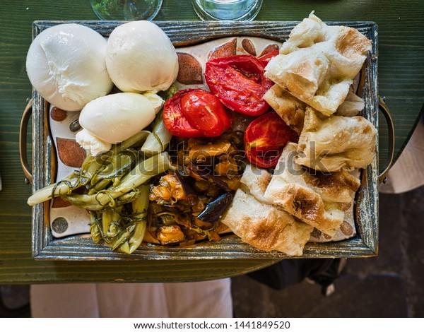 Orta San Giulio, Lake Orta, Italy - June 29, 2019 Cutting board based in focaccia, tomatoes, mozarella, burrata and antipasto.