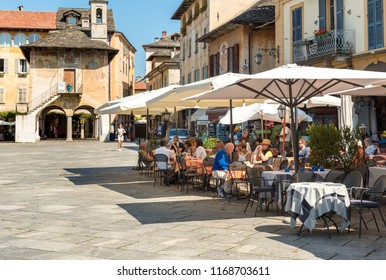 Orta San Giulio, Novara, Italy - August 28, 2018: People enjoying the outdoor bar in the historic center of ancient village of Orta San Giulio, located on the coast of Lake Orta in Piedmont, Italy