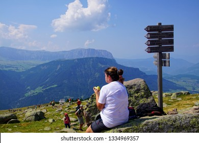 ORTESEI, ITALY - AUG 5, 2018 - Young woman takes a rest on the trail in the Dolomites Alps, Italy