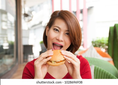 Orthodontic women enjoy eating with her burger in hands,asian women open her mouth for biting burger,selective focus
