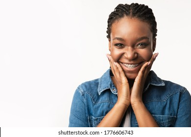 Orthodontics Concept. Joyful Black Girl With Brackets Cupping Face In Hands Smiling To Camera On White Background. Studio Shot