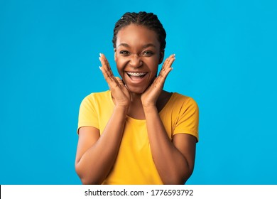 Orthodontics Treatment. Excited African Girl With Brackets Cupping Face In Hands Smiling To Camera Posing In Studio On Blue Background.