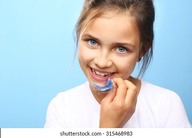 Orthodontics.Pretty girl with colored orthodontic appliance