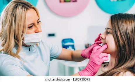 Orthodontist fixing girl's dental braces
