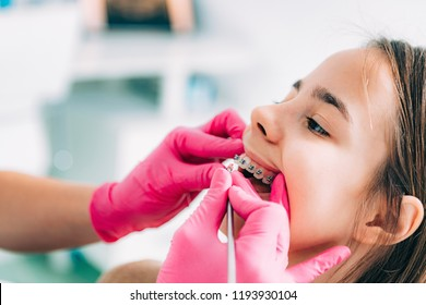 Orthodontist fixing girl's dental braces