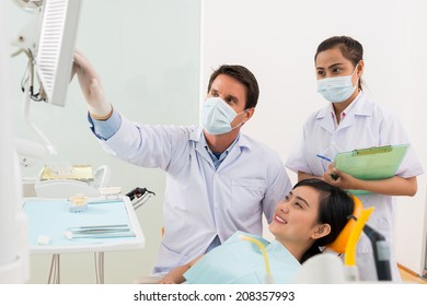 Orthodontist showing something on the monitor to female patient