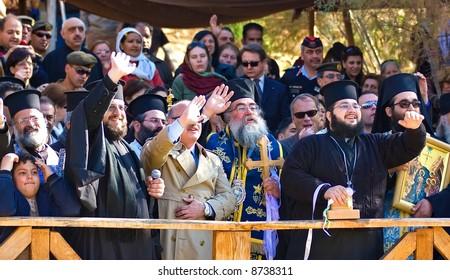 Orthodox Celebrating Jesus Baptism, waving hands for peace, Jordan River, Israel