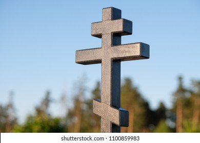 Orthodox christian stone cross in the cemetery. Summer. Sunny weather. Orthodox religion