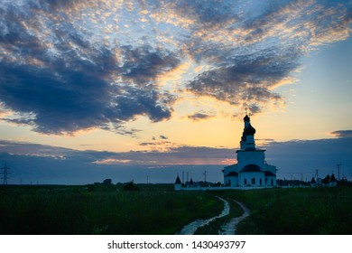 Orthodox church in the village near the field at sunset in the Moscow region