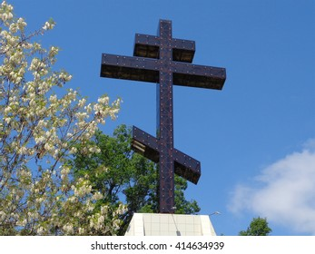 Orthodox cross and blooming white acacia against blue sky