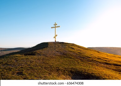 Orthodox cross on a hill in the sunset