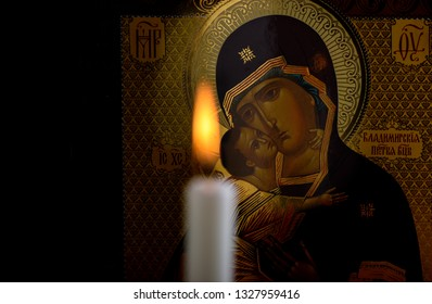 Orthodox icon of the Mother of God and baby Jesus and a blurred burning candle in front of icon. Focus on the icon.
