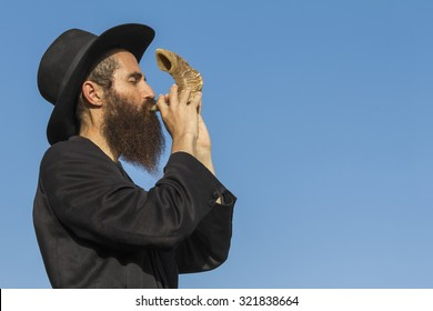Orthodox Jewish man blast in Shofar at Rosh Hashana holiday on blue sky background