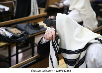 """Orthodox Jewish man covered in prayer shawl known as """"tallit"""", grasps the fringes of the shawl and makes a blessing"""