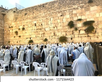 Orthodox Jewish men in Tallit prayer shawls standing for Shacharit sunrise prayer at the Western/Wailing Wall or Kotel, the holiest place in Judaism; Jerusalem Israel