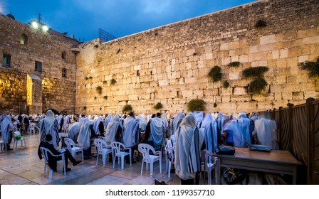 Orthodox Jewish men in Tallit prayer shawls standing from before dawn for Shacharit sunrise prayer at the Western/Wailing Wall or Kotel, the holiest place in Judaism; Jerusalem Israel