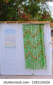 Orthodox Jewish Sukkah during Sukkot holiday in Jerusalem, Israel. Jewish festival of Sukkot. Traditional Fabric succah hut decorated with printed pattern and pomegranate fruit  festive decor.