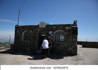 "Orthodox Jewish women walk into the tomb of Rabbi Yossi Hagalili to pray. Sign above entrances translates to ""Grave of Rabbi Yossi Hagalili"""