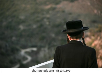 Orthodox Jews, dressed in a black coat and hat, looking at the landscape and the mountains