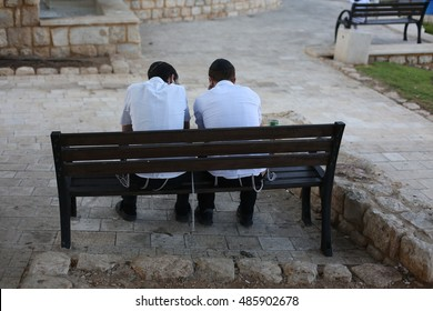 Orthodox Jews sit together on a bench in the park