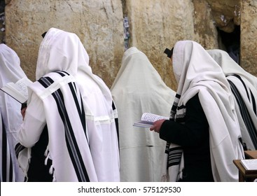 Orthodox Jews wearing tallit prayer shawls praying at the Western wall