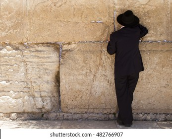 orthodox man with black clothes and hat praying at the Wailing Wall, Jerusalem