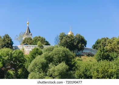 Orthodox monastery with its Golden dome and tower rises above the trees on the background of clear blue sky. Vladimir city