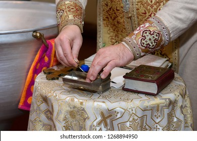 Orthodox priest with tools for the ceremony.  Baptism in the temple of babies.