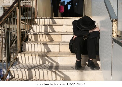 Orthodox religious Jewish man sits crouched over on stairs, with his head in his arms, seemingly in despair