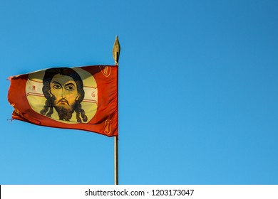 Orthodox Russian church red flag with icon, cross and jesus on a spear fluttering in the wind against the blue sky. background with copy space for design or text