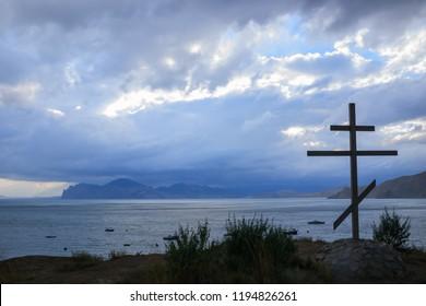 Orthodox wood tomb cross on the rock, view to Black sea, Crimea