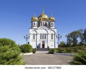 Orthodoxy church temple with golden domes: Holy Protection of the Mother of God. Front view. Greenery with red roses and blue sky around it. Donetsk, Ukraine, 2016 year.