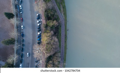 Orthogonal aerial view of the Tiber river in Rome. To the side passes the road called Lungotevere. There are trees and cars parked.