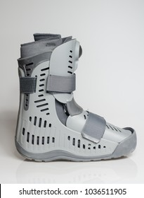 A orthopaedic grey plastic boot ankle brace injury protecting boot, with velcro straps isolated on a white background. Broken feet broken foot protection.