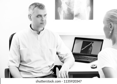 Orthopedic doctor explaining patient in his offisce. X-ray.