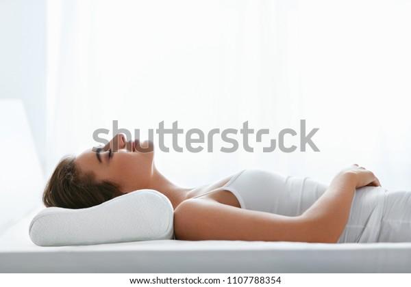 Ортопедическая подушка. Женщина, лежащая в постели