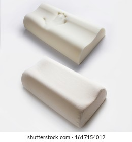 Orthopedic pillows, memory foam  on white background. Two pillows piled against white background. Handprint on the pillow. Comfortable bedding with orthopaedic, therapeutic effect. Memory foam materia