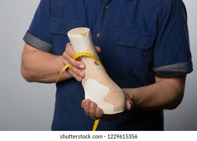 Orthopedic shoemaker with measuring tape and a wooden last
