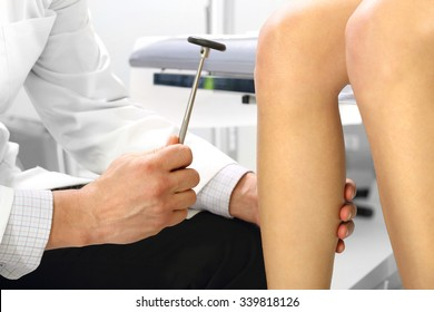Orthopedic surgeon examining the knee reflex. The doctor checks the physiological reflex, the test hammer