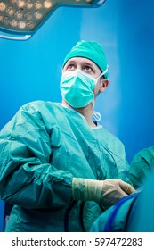 Orthopedic surgeon portrait in the hospital while performing keyhole arthroscopic surgery on human patient as definitive treatment option.