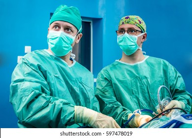 Orthopedic surgeons portrait in the hospital while performing keyhole arthroscopic surgery in team on a human patient as definitive treatment.