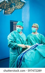 Orthopedic surgeons portraiture in the hospital while performing keyhole arthroscopic surgery in team on a human patient after trauma as definitive treatment option.