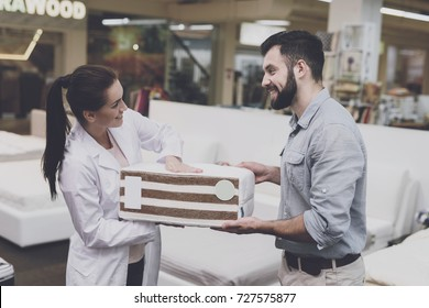 An orthopedic woman shows the man a sample of the mattress he wants to buy. A woman shows a man a sample of a mattress. He looks at him carefully. he wants to buy a mattress for himself