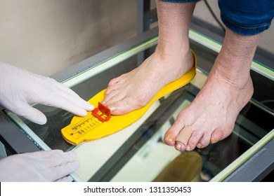 Orthopedics and medicine. Young Caucasian doctor hands man tattoo latex gloves size measurement shape of the foot for the manufacture of individual orthopedic insole. Flatfoot and foot diseases.