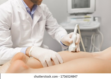 Orthopedist doctor doing ultrasound examination of patient's leg veins in his office. Young woman passing ultrasound scan in clinic. Doctor work. Medical research.