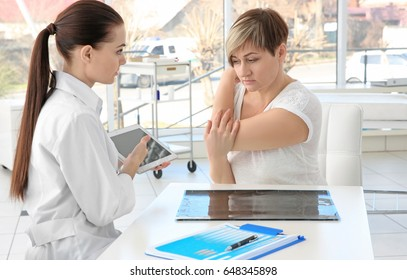 Orthopedist examining middle-aged woman in clinic