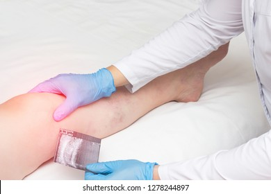 The orthopedist holds a picture of an ultrasound and examines a woman s knee, diagnoses arthrosis and arthritis, copys space